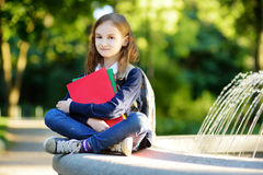 Adorable little schoolgirl in a city park on bright autumn day Royalty Free Stock Images