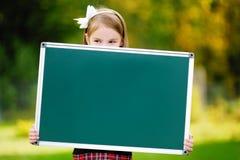 Adorable little schoolgirl holding a chalkboard Lizenzfreie Stockfotografie