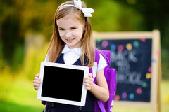 Adorable little schoolgirl holding digital tablet Stock Image