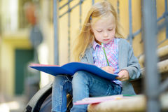 Adorable little schoolgirl studying outdoors on bright autumn day Royalty Free Stock Photo