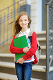 Adorable little schoolgirl studying outdoors on bright autumn day Royalty Free Stock Images