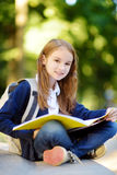 Adorable little schoolgirl studying outdoors on bright autumn day. Young student doing her homework. Education for small kids. Back to school concept royalty free stock photo
