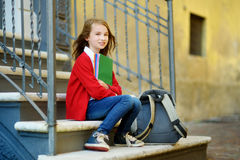 Adorable little schoolgirl studying outdoors on bright autumn day. Young student doing her homework. Education for small kids. Back to school concept royalty free stock images