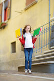 Adorable little schoolgirl studying outdoors on bright autumn day. Young student doing her homework. Education for small kids. Royalty Free Stock Photography