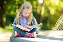 Adorable little schoolgirl studying outdoors on bright autumn day. Young student doing her homework. Education for small kids. Royalty Free Stock Photo