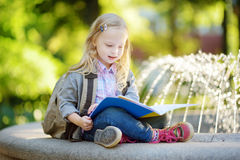 Adorable little schoolgirl studying outdoors on bright autumn day. Young student doing her homework. Education for small kids. Royalty Free Stock Image