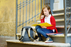 Adorable little schoolgirl studying outdoors on bright autumn day. Young student doing her homework. Education for small kids. Back to school concept stock images