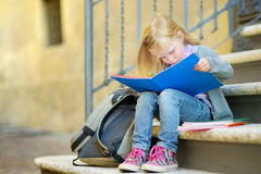 Adorable little schoolgirl studying outdoors on bright autumn day. Young student doing her homework. Education for small kids. Stock Images