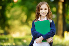 Adorable little schoolgirl studying outdoors on bright autumn day. Young student doing her homework. Education for small kids. Back to school concept Stock Photos