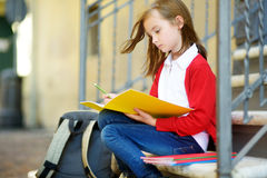 Adorable little schoolgirl studying outdoors on bright autumn day. Young student doing her homework. Education for small kids. Stock Image