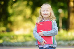 Adorable little schoolgirl studying outdoors on bright autumn day. Young student doing her homework. Education for small kids. Stock Photography