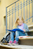 Adorable little schoolgirl studying outdoors on bright autumn day. Young student doing her homework. Education for small kids. Stock Photos