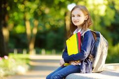 Adorable little schoolgirl studying outdoors on bright autumn day. Young student doing her homework. Education for small kids. Back to school concept stock photography