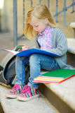 Adorable little schoolgirl studying outdoors on bright autumn day. Young student doing her homework. Education for small kids. Royalty Free Stock Photos