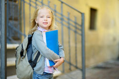 Adorable little schoolgirl studying outdoors on bright autumn day. Young student doing her homework. Education for small kids. Back to school concept royalty free stock photos