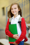 Adorable little schoolgirl studying outdoors on bright autumn day. Young student doing her homework. Education for small kids. Stock Photo