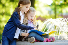 Adorable little schoolgirls studying outdoors on bright autumn day. Young students doing their homework. Education for small kids. Royalty Free Stock Image