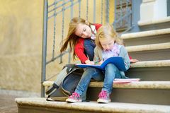 Adorable little schoolgirls studying outdoors on bright autumn day. Young students doing their homework. Education for small kids. Stock Photo