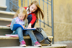Adorable little schoolgirls studying outdoors on bright autumn day. Young students doing their homework. Education for small kids. Royalty Free Stock Photography
