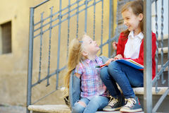 Adorable little schoolgirls studying outdoors on bright autumn day. Young students doing their homework. Education for small kids. Royalty Free Stock Images