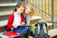 Adorable Little Schoolgirls Studying Outdoors On Bright Autumn Day. Young Students Doing Their Homework. Education For Small Kids. Stock Photography
