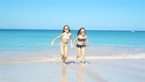 Adorable little girls relaxing on the beach. Adorable little sisters at beach during summer vacation stock video footage
