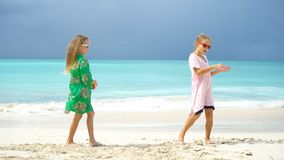Adorable little girls have a lot of fun on the beach. Two beautiful kids dancing on the seashore. Adorable little sisters at beach during summer vacation stock video