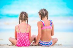Adorable little girls playing with sand on the beach. Back view of kids sitting in shallow water and making a sandcastle Royalty Free Stock Photos