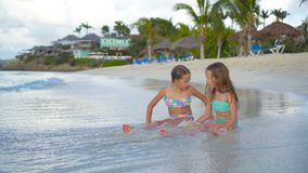 Adorable little girls relaxing on the beach playing in shallow water. Adorable little sisters at beach during summer vacation stock footage