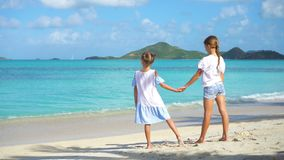 Adorable little girls walking on the beach and having fun together. Adorable little sisters at beach during summer vacation stock footage