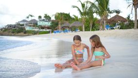 Adorable little girls relaxing on the beach. Adorable little sisters at beach during summer vacation. Kids in shallow water playing together stock video