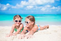 Portrait of kids lying on warm white sand Stock Image