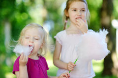 Adorable little sisters eating candy-floss Stock Photo