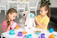 adorable little sisters pretending to have tea party together stock image