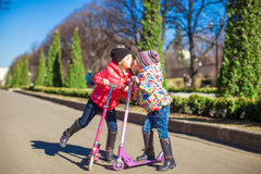 Adorable little sisters ride scooters on a warm sunny spring day Royalty Free Stock Photos