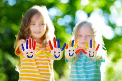 Adorable little sisters with their hands painted having fun outdoors. On bright summer day royalty free stock photos