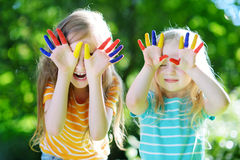 Adorable little sisters with their hands painted having fun outdoors. On bright summer day stock photography