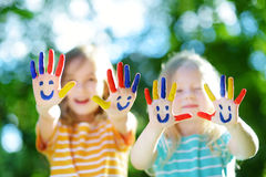 Adorable little sisters with their hands painted having fun outdoors. On bright summer day stock image