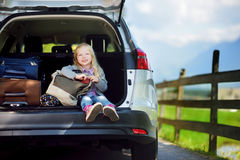 Adorable little sitting in a car before going on vacations with her parents. Kid ready to travel by car Royalty Free Stock Image