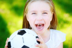Adorable little soccer fan cheering on hot summer day at park. Adorable little soccer fan cheering on hot summer day Stock Photo