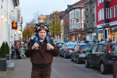 Adorable little son and father walking through city on evening. Royalty Free Stock Images