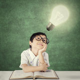 Adorable little student looking at light bulb Stock Photos