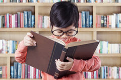 Adorable little student reads book in library Stock Photography