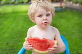 Adorable little toddler boy with blond hairs eating watermelon i Stock Images