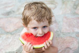 Adorable little toddler boy with blond hairs eating watermelon i Stock Photos