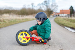 Adorable little toddler boy sad about his broken bicycle, sittin Royalty Free Stock Photos