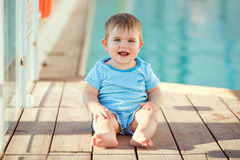 Adorable little toddler boy striped suit sitting on the backgrou Stock Images