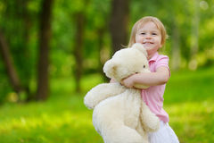 Adorable little toddler girl with a big teddy bear Stock Images