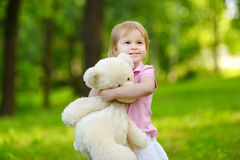 Adorable little toddler girl with a big teddy bear Stock Photos