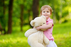 Adorable little toddler girl with a big teddy bear Stock Image